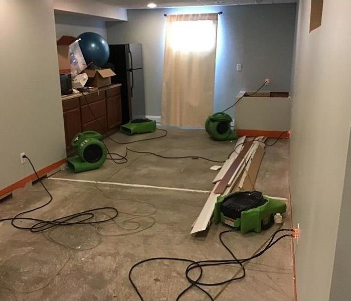 Room of a home with flooring removed and four air movers set up in the area.