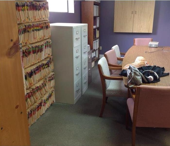 Carpeted office room with conference table, filing cabinets, files and bookshelvles.