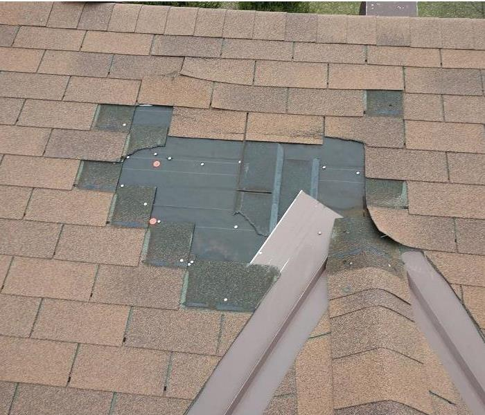 Roof of a home with missing shingles.