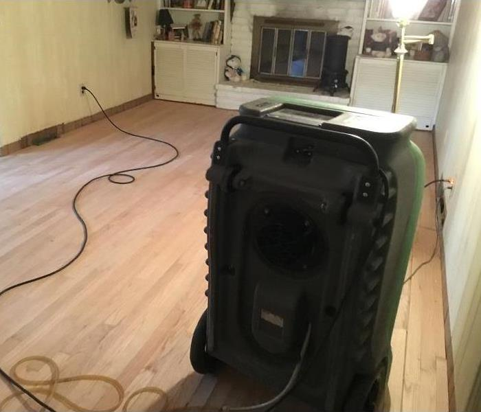 Room of a home with hardwood floors and a dehumidifier set up in the room.