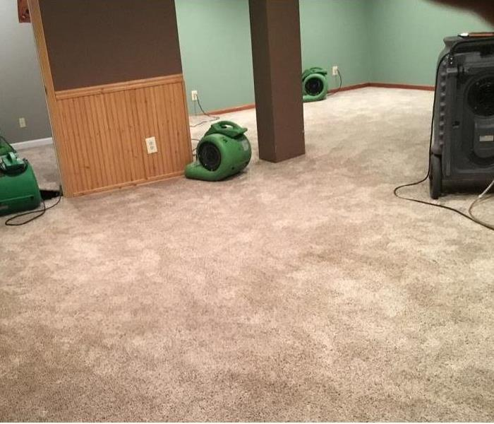 Carpeted room with several air movers and a dehumidifier placed throughout the room.