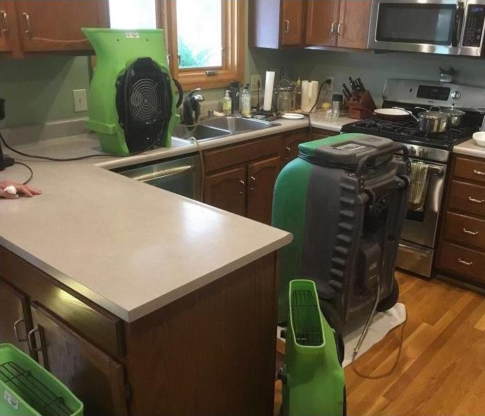 Kitchen of a home with air movers and a dehumidifier set up.